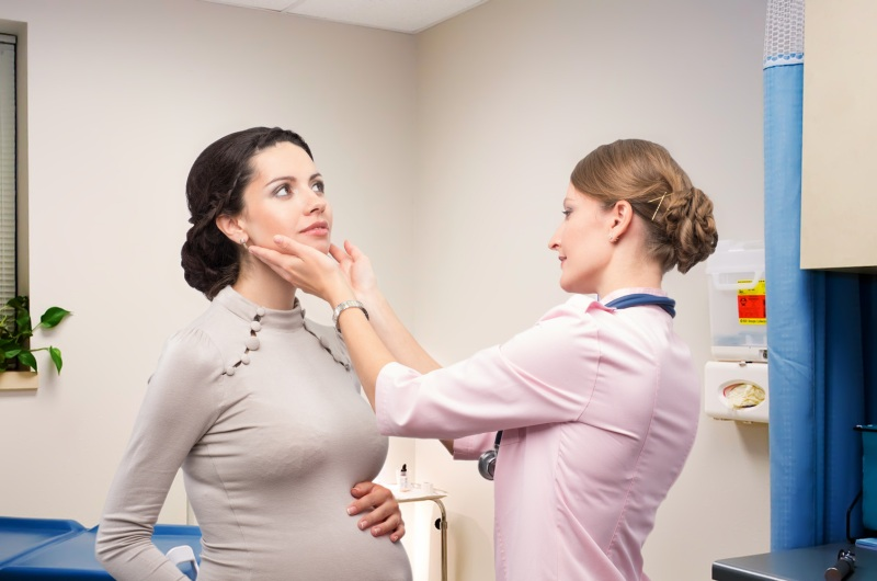 Doctor endocrinologist checking thyroid pregnant