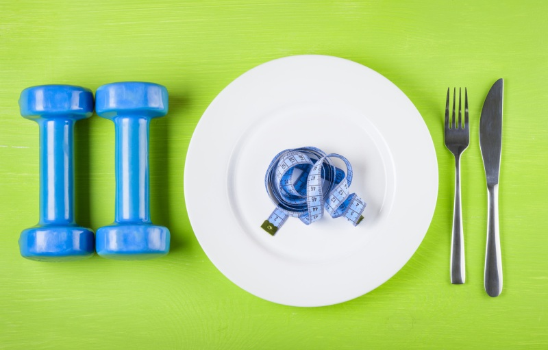 The concept of a healthy lifestyle, diet, sports, weight loss, anti-obesity, exercise, healthy diet. Centimeter on a plate, knife, dumbbells and fork, top view, closeup