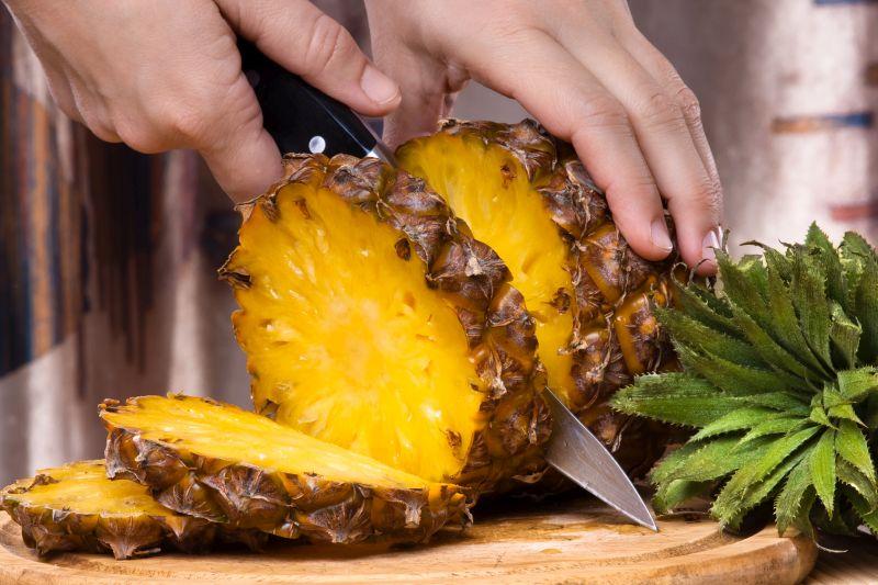 hands slicing pineapple, closeup