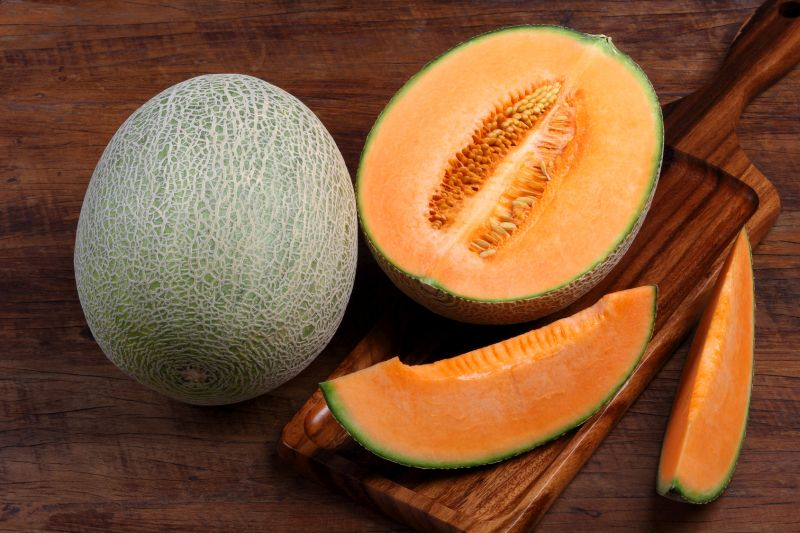 Organic cantaloupe with utensils on wooden table